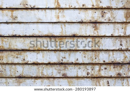 Close up of a rusted metal roll up door shows the damage that salty air near a port can cause.  - stock photo