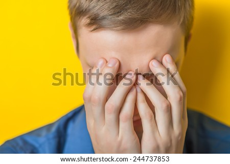 Close up of a sad casual young man with hands to his face at home - stock photo