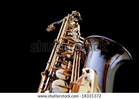 Close up of a saxophone isolated in black background - stock photo