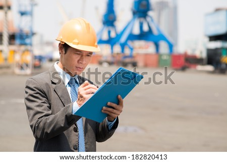Close-up of a seaport inspector at work  - stock photo