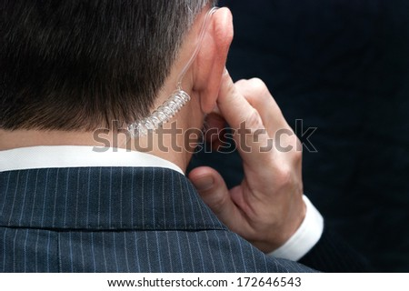Close-up of a secret service agent listening to his earpiece, behind. - stock photo
