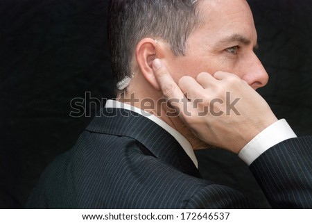 Close-up of a secret service agent listening to his earpiece, side. - stock photo