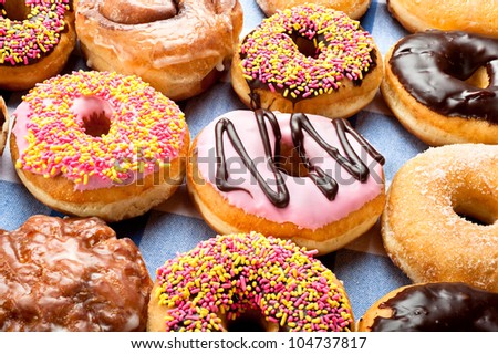 Close up of a selection of colorful donuts.  Focus is on middle row. - stock photo