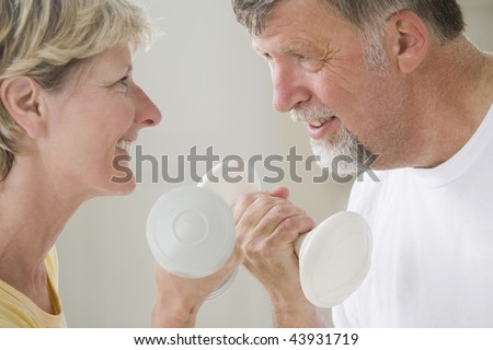 Close-up of a senior couple holding hand weights and smiling - stock photo