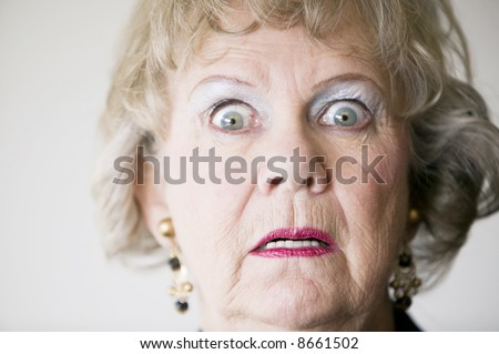 Close-up of a senior woman with a horrified look on her face. - stock photo