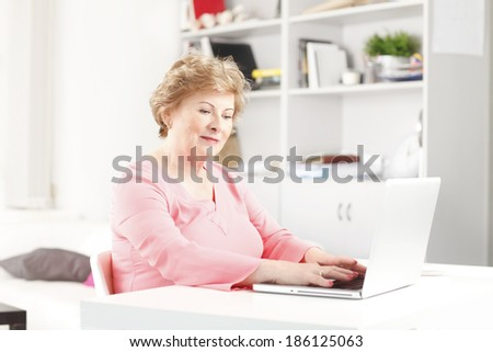 Close-up of a senior women sitting at desk and working laptop. Small business.  - stock photo