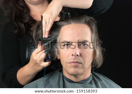 Close-up of a serious man looking to camera while his long hair is cut off for a cancer fundraiser. - stock photo