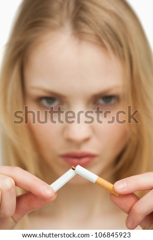 Close up of a serious woman breaking a cigarette against white background - stock photo