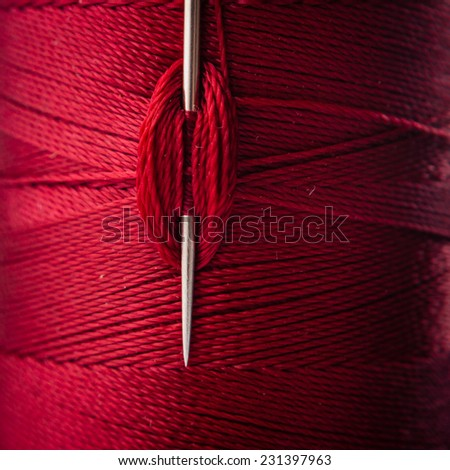 close up of a sewing needle and red thread - stock photo