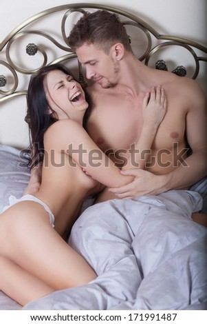 Close up of a sexy couple kissing and playing in bed. sex toys. - stock photo