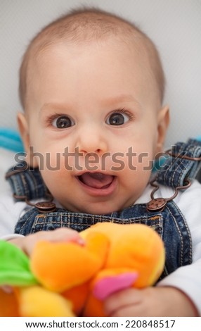 Close up of a six months old baby boy making funny faces. - stock photo