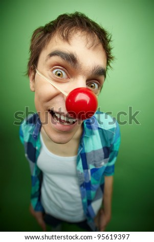 Close-up of a slightly mad guy with clown nose celebrating fools day - stock photo