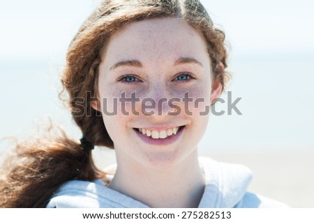 close up of a smiling freckle faced teen girl - stock photo