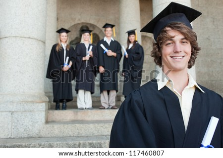 Close-up of a smiling graduate smiling with her friends in background in front of the university - stock photo