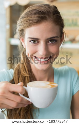 Close-up of a smiling young woman drinking coffee in the coffee shop - stock photo