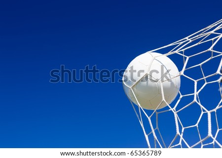 Close-up of a soccer ball (football) going into the back of the net with a blue sky background. - stock photo
