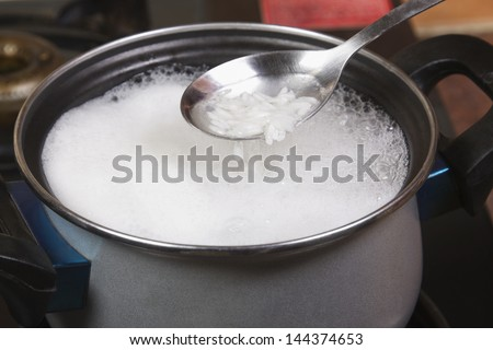 Close-up of a spatula over a pan of rice boiling on a stove - stock photo