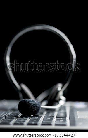 Close-up of a stereo headset on the keyboard of a computer, on black background - stock photo