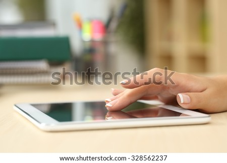 Close up of a student hand searching in a tablet on a desk at home - stock photo