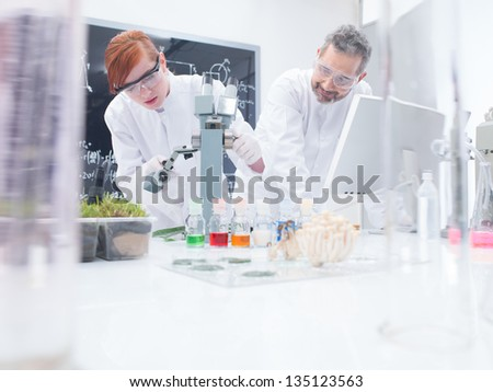 close-up of a student in a chemistry lab around lab tools and colorful liquids conducting an experiment under microscope under the observation of her teacher - stock photo
