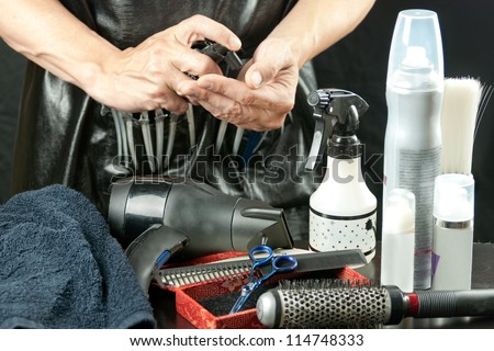 Close-up of a stylist surrounded by his tools spraying mousse into his hand. - stock photo