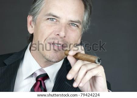 Close-up of a successful businessman smoking a cigar. - stock photo