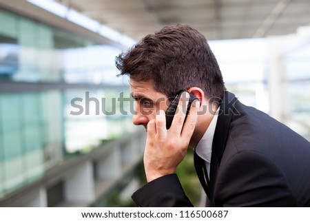 Close-up of a successful young business man talking on cell phone at modern office - stock photo