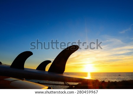 close up of a surfboard on a car roof at sunset - stock photo
