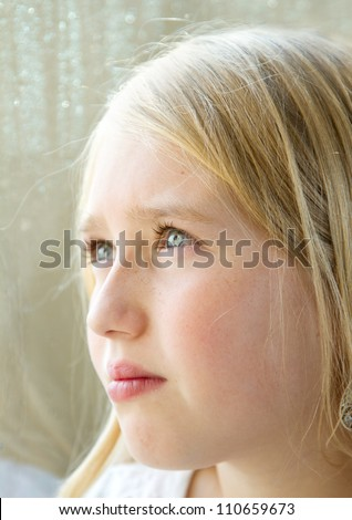 close-up of a teen or child looking out a rainy window - stock photo