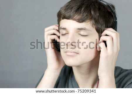 Close-up of a teen with closed eyes holding his headphones to his ears. - stock photo