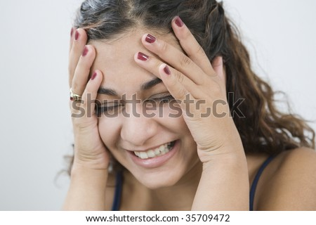 Close-up of a teenage girl laughing with her head in her hands - stock photo