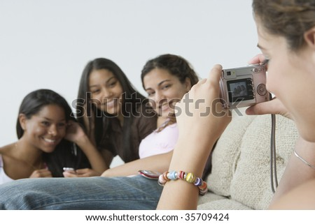 Close-up of a teenage girl taking a picture of her friends with a digital camera - stock photo
