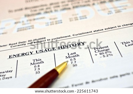 """Close up of a utility bill and ball pen showing a 60% energy usage increase over last month. In the background """"PAST DUE"""" can be read in big white letters on faded red background. - stock photo"""