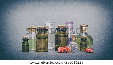 Close-up of a variety of small glass vials filled with natural aromatic essential oils. Toned image in retro style - stock photo