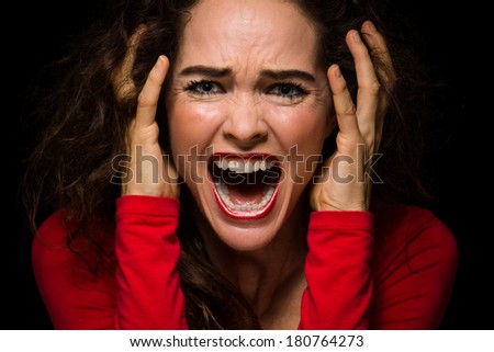 Close-up of a very angry, upset and desperate woman, screaming. - stock photo