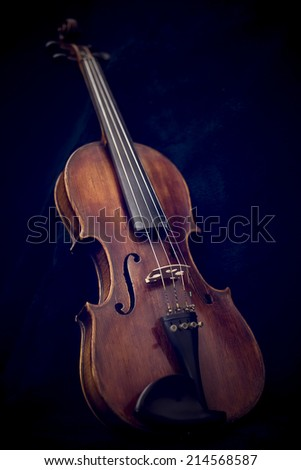 Close up of a violin isolated on a dark background - stock photo