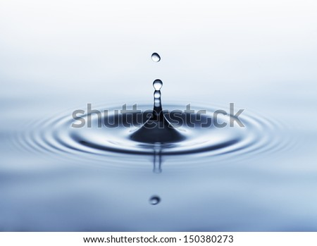 Close-up of a water drop impact with water surface, causing rings on the surface. - stock photo