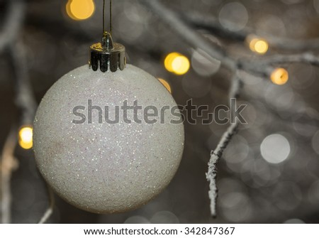 Close up of a white glittery christmas bauble hanging from a contemporary christmas tree. - stock photo