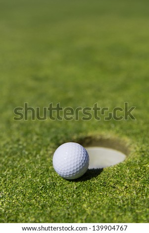 close up of a white golf ball on the edge of a hole with out a flag - stock photo