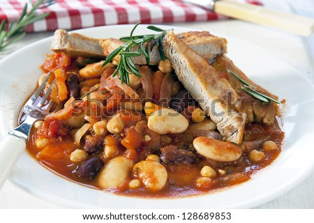 Close-up of a white plate with a meal of Boston Pork complete with beans, carrot and onions garnished with rosemary - stock photo