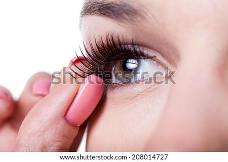 Close-up of a woman applying false eyelashes - stock photo