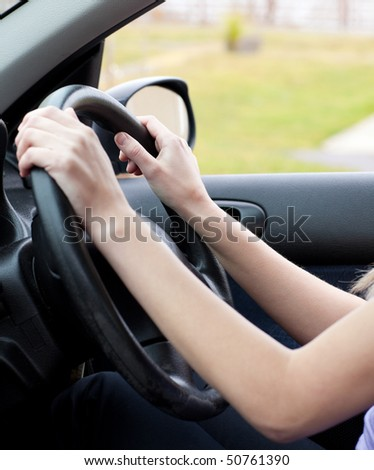 Close-up of a woman at the wheel in her new car - stock photo