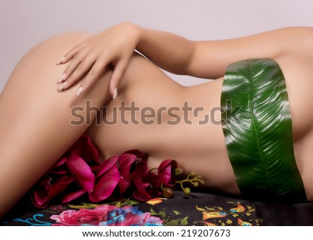 Close up of a woman beautiful body with flower - stock photo