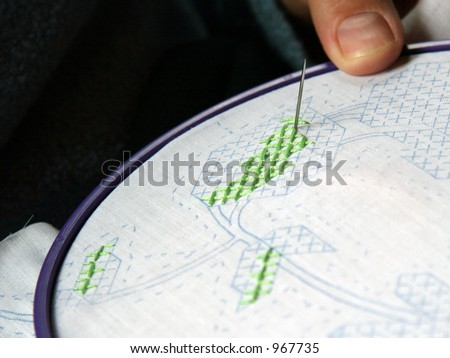 Close up of a Woman Cross Stitching green flower for a quilt - stock photo
