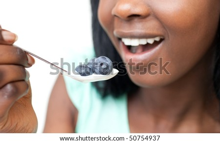 Close-up of a woman eating a yogurt with blueberries against a white background - stock photo