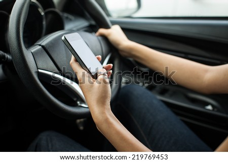 Close-up of a woman hand sending a text while driving, focus on hand - stock photo