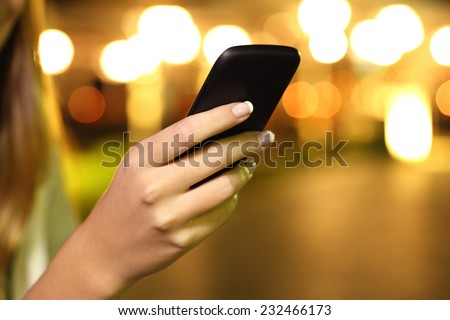 Close up of a woman hand using a smart phone in the night with lights in the background - stock photo