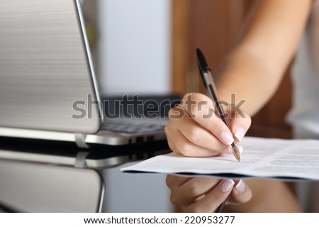 Close up of a woman hand writing a contract with a laptop beside at home or office - stock photo