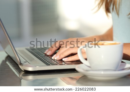 Close up of a woman hands typing in a laptop in a coffee shop terrace in the street - stock photo