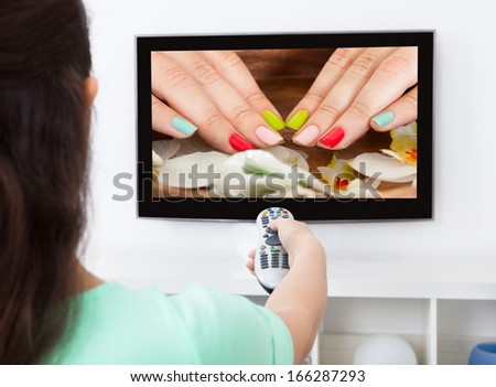 Close-up Of A Woman Holding Remote Control Changing Television Channel - stock photo